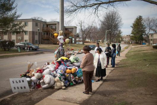 FERGUSON, MO - MARCH 14: Visitors look over a memorial to Michael Brown outside the Canfield Green apartments where he was shot and killed by a police officer last August on March 14, 2015 in Ferguson, Missouri.  The town of Ferguson has experienced many protests, which have often been violent, since Brown's death. On Wednesday evening two police officers were shot while they were securing the Ferguson police station during a protest.  (Photo by Scott Olson/Getty Images)