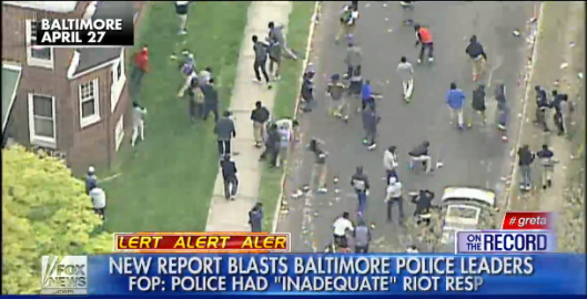 Rock-throwing rioters chase police down a Baltimore street.