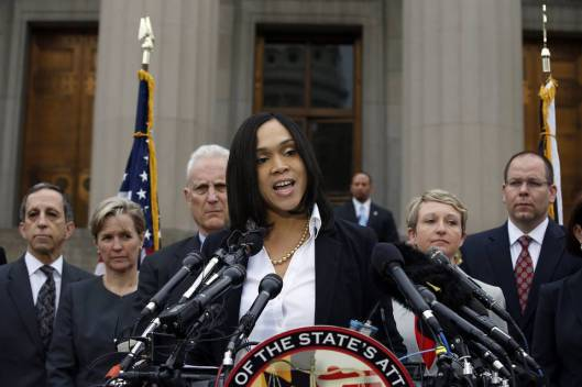 Who is that grim, white-haired man behind Marilyn Mosby? credit: wsj.com