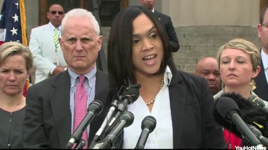 Michael Schatzow (white hair) is often depicted behind Marilyn Mosby, scowling. credit: huffington post